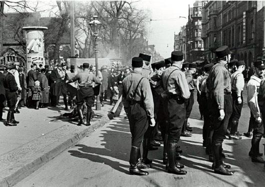 1. April 1933: SS-Männer und Passanten vor dem besetzten Gewerkschaftshaus. Auf dem Gehweg verbrannte Fahnen der Gewerkschaften und der SPD. Foto Walter Ballhause. Walter-Ballhause-Archiv, Plauen
