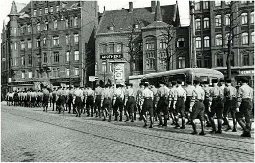 Uniformierte Nationalsozialisten marschieren nach Besetzung des Gewerkschaftshauses über den Klagesmarkt in Richtung Nordstadt, 1. April 1933. Foto von Walter Ballhause. Walter Ballhause Archiv, Plauen